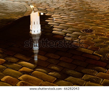 Tallinn town hall at night in Raekoya square showing the floodlit spire and tower of the hall reflected in a rain pool on the cobbled streets - stock photo