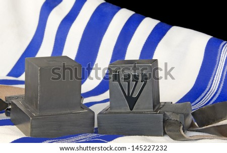 Tallit and tefillin.Pair of black boxes with leather straps.Worn by Jewish men during prayer.White wool cloth garment with blue stripes indicate Sephardic style,custom.Isolated on a black background. - stock photo
