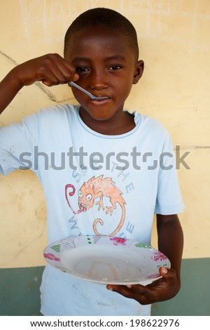 TAMALE, GHANA - MARCH 22: Unidentified young African boy pose with empty plate on March 22, 2014 in Tamale, Ghana. Tamale is the hub of all commercial activity in Northern Region of Ghana.