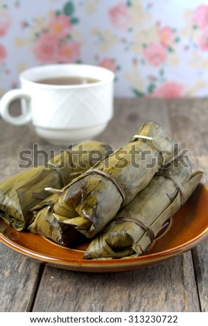 Tamales are a mix of meat and vegetables with rice or corn folded in a banana leaf and then steamed. - stock photo
