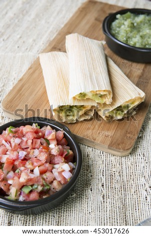 Tamales fresh out of the steamer on a wooden cutting board with pico de gallo and salsa verde toppings.