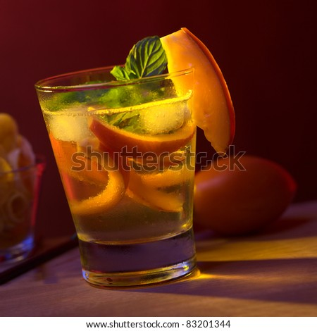 Tamarillo cocktail (Selective Focus, Focus on the tamarillo slice on the rim of the glass) - stock photo
