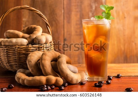 Tamarind juice - Delicious sweet drink tamarind and ice with mint leaves on rustic wooden table. Selective focus and toned image. Copy space.
