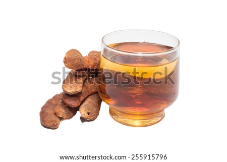 Tamarind juice in a glass surrounded by fresh ripe tamarinds isolate on white - stock photo
