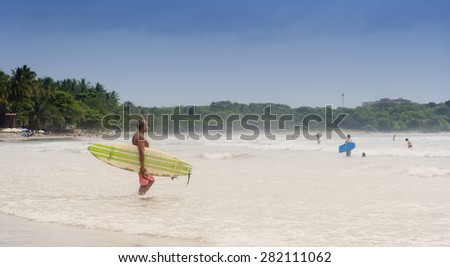 TAMARINDO, COSTA RICA - SEPTEMBER 13, 2008: Young afro-american man walking with his surfboard into sea on the beach in Tamarindo, Costa Rica. Tamarindo is a leading surfer hotspot. - stock photo