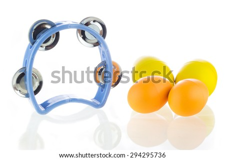 Tambourine and egg maracas shaker on a white background. - stock photo
