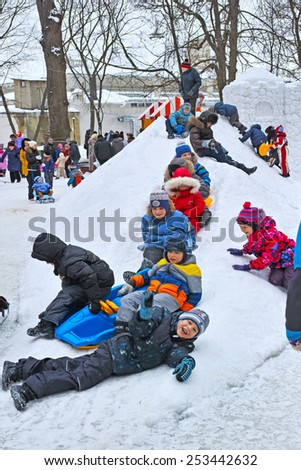 Tambov, Russia - February 15, 2015: Maslenitsa (pancake week, shrovetide) - carnival of farewell winter and meeting spring in Tambov.  Children slide down a snowy hill built in the park.   - stock photo