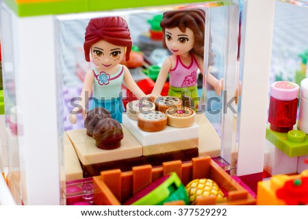 Tambov, Russian Federation - February 09, 2016 Lego girls choose baking in the shop. Photo taken through shop window. Studio shot.