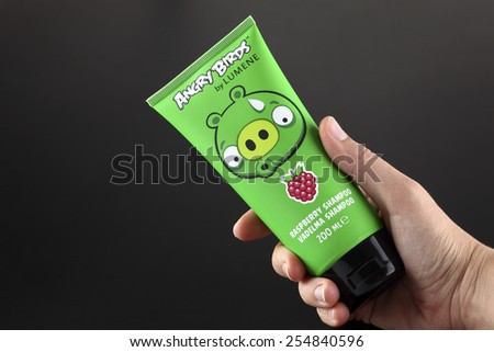 Tambov, Russian Federation - September 22, 2013 Angry Birds by LUMENE in human hand on black background. It is Raspberry Shampoo with Bad Piggies image by collection of body care products.