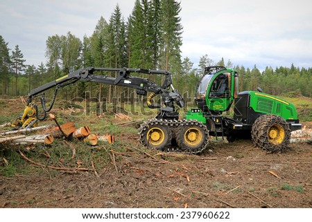 TAMMELA, FINLAND - AUGUST 31, 2014: John Deere 1270E wheeled harvester at a forest logging site. The The 1270E was introduced in 1996 and it has a large 9.0-liter engine and CH7 Harvester boom. - stock photo