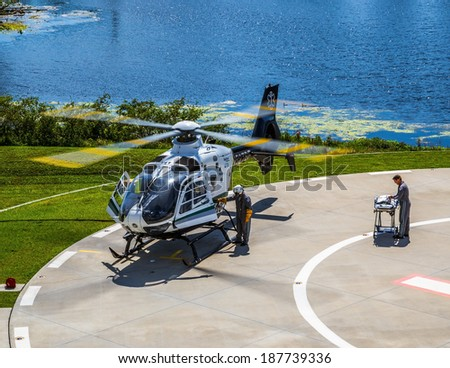 Tampa, Florida April 4th, 2014 Bayflite Trauma Rescue Helicopter. The crew preparing to respond to an accident scene. The pilot fuels the chopper and a medic readies the stretcher. - stock photo