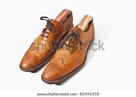 Tan fashionable male brogue shoes on white background - stock photo