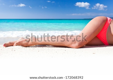 Tan slim legs lying on white sandy beach near sea, no face - stock photo