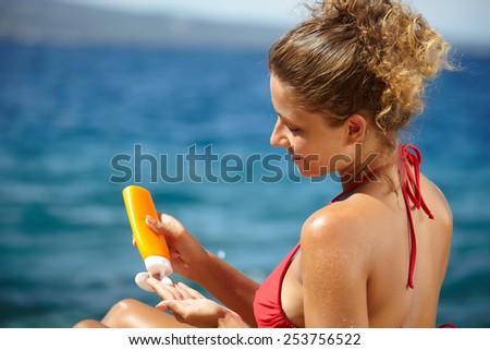 Tan woman applying sun protection lotion  - stock photo