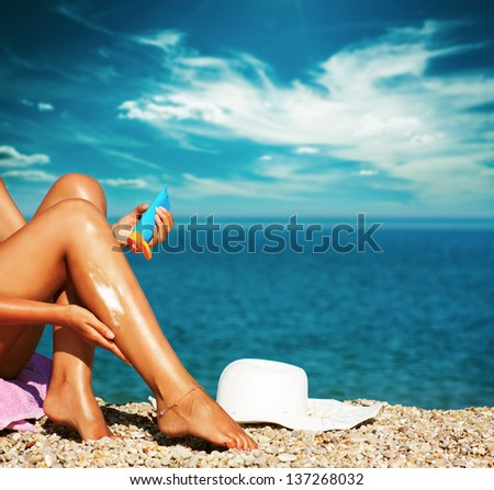 Tan Woman Applying Sunscreen on Legs - stock photo
