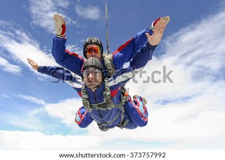 Tandem jump in the sky with clouds. - stock photo