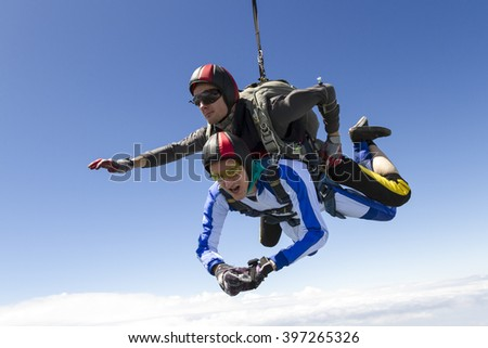 Tandem jump. The instructor and the student in freefall. - stock photo