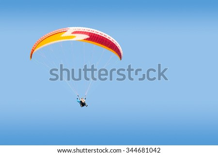 Tandem paraglider free gliding at high altitude in deep blue sky - stock photo