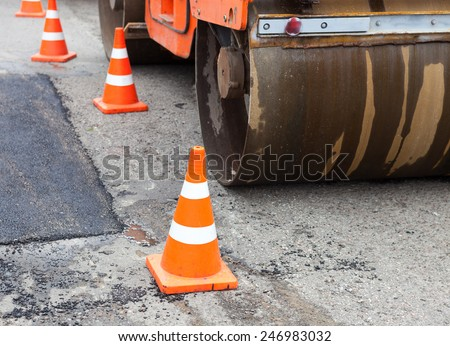 Tandem road roller and traffic cones on the road construction. - stock photo
