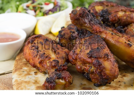 Tandoori chicken legs served on top of a naan bread, with salad, chili sauce, raita and lemon wedges. - stock photo