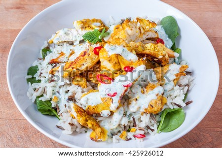 Tandoori chicken, rice and spinach dish in a white bowl
