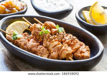 Tandoori chicken skewers, served with yogurt, lemon wedges and mango chutney. - stock photo
