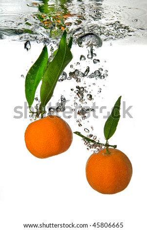 tangerine dropped into water with bubbles on white - stock photo