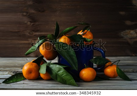 Tangerine in blue ladle on the table - stock photo