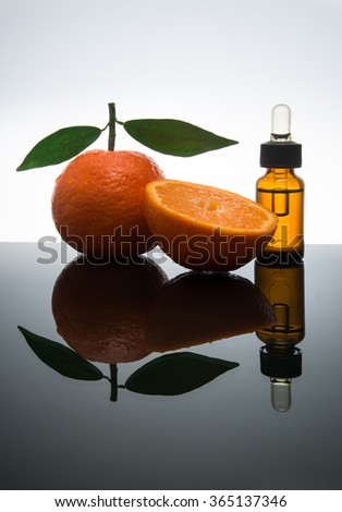 Tangerine / mandarin essential oil bottle with dropper  - stock photo