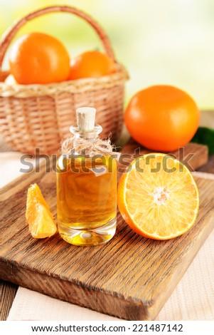 Tangerine oil on table on light background - stock photo