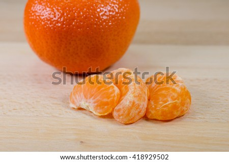 tangerine segments and whole tangerine on a wooden table - stock photo
