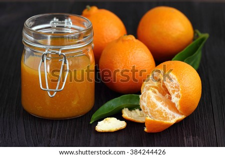 tangerines and  jam in glass jar - stock photo