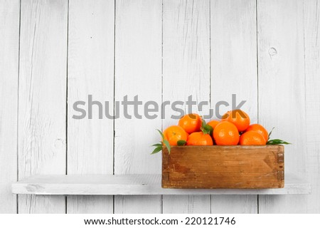 Tangerines in a box on a wooden shelf. - stock photo