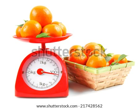 Tangerines on scales and in a basket on a white background.