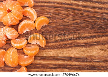 Tangerines slices lying on wooden table with place for text - stock photo