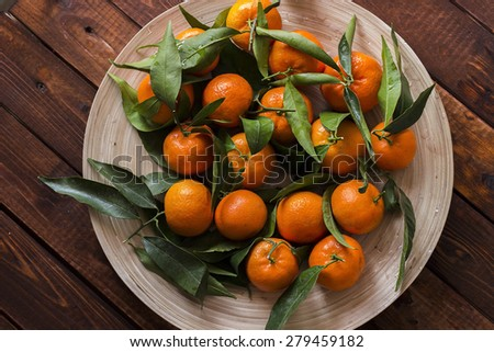 Tangerines with leaves on a wooden - stock photo
