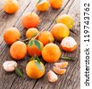 Tangerines with leaves on a wooden table. - stock photo