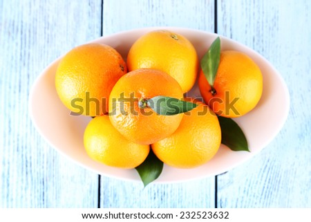 Tangerines with leaves on plate on wooden background