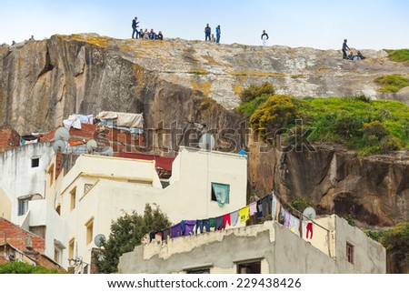 Tangier, Morocco - March 22, 2014: Old traditional colorful living houses of Medina in poor area of Tangier, Young people are relaxing on coastal rock - stock photo