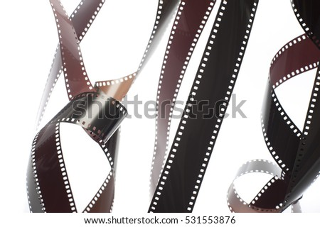 Tangle of unrolled exposed 35mm film strips over a white background in a retro photography concept