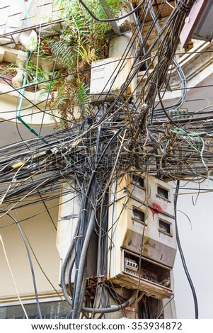 Tangled and messy electric cables and wires in all directions at an alley in Hanoi, Vietnam. Urban problem in developing economies/countries