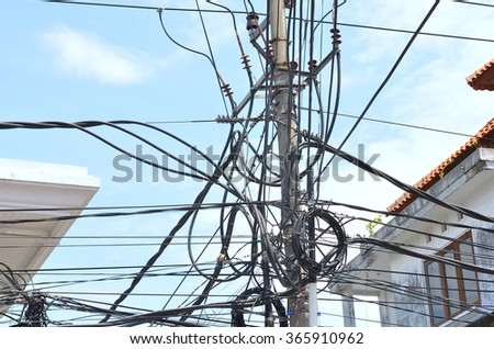 Tangled and Un safe power lines in Asia - stock photo