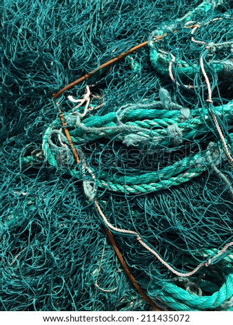 Tangled teal fishing net and rope - stock photo