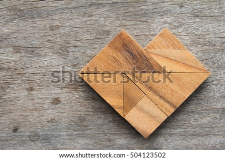 Tangram puzzle in heart shape on wooden table