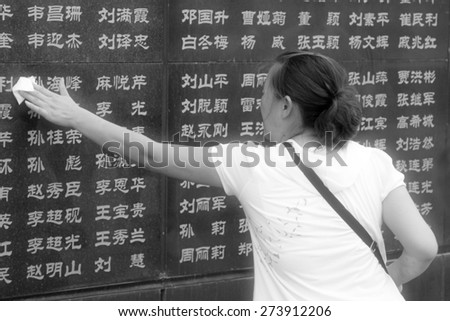 Tangshan City, July 28: A woman wipes the dust on the names of relatives died in the earthquake, before the Tangshan Earthquake Memorial Wall on July 28, 2012, Tangshan City, Hebei Province, China.