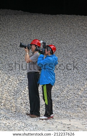 TANGSHAN - JUNE 14: Two photographers taking photoes in gray stone background, on June 14, 2014, Tangshan city, Hebei Province, China