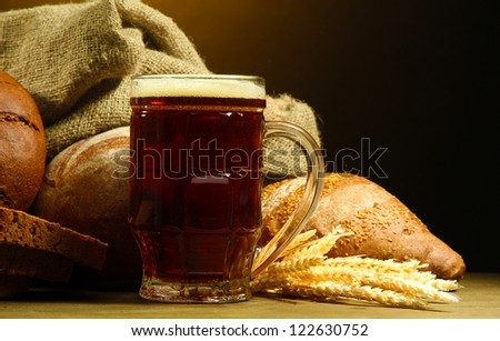 tankard of kvass and rye breads with ears, on wooden table on brown background - stock photo