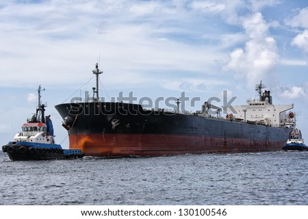 Tanker ship being pulled by tugboats - stock photo