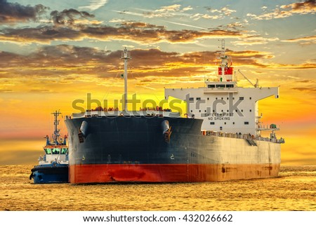Tanker ship on sea in the rays of the setting sun. - stock photo