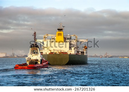 Tanker ship with escorting tug in port. - stock photo